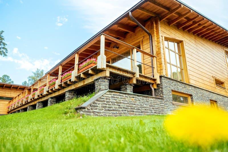 Fassade eines schönen Holzhauses mit grünem Garten lizenzfreies stockbild