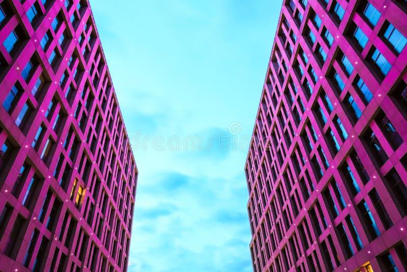 Fassade von Wolkenkratzern mit schöner rosa Beleuchtung vor dem hintergrund des blauen Himmels an der Dämmerung, Dnepr-Stadt stockfotos