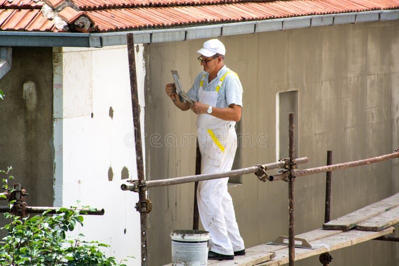 Fassaden-Gipser mit weißer Uniform ist auf Gestell stockfotos