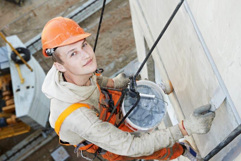 Fassaden-Gipserarbeitskraft bei der Arbeit stockfotos