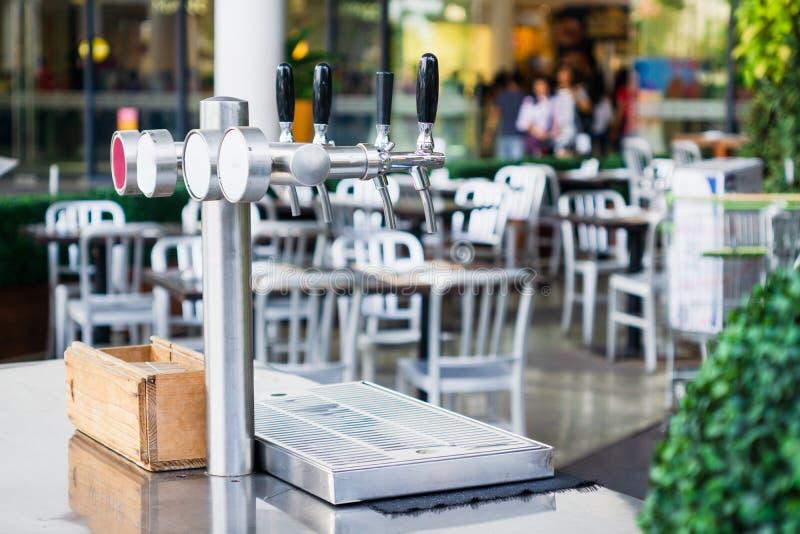 Fassbier-Zufuhrturm 4 Hahn, Abschluss im Freien oben einer Reihe des Metallzapfen-Fassbierhahns auf der Bar stockbild