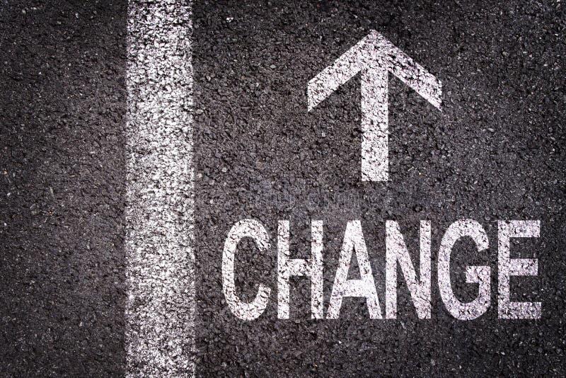 Fassen Sie Änderung und einen Pfeil, der auf eine Asphaltstraße geschrieben wird ab lizenzfreies stockfoto