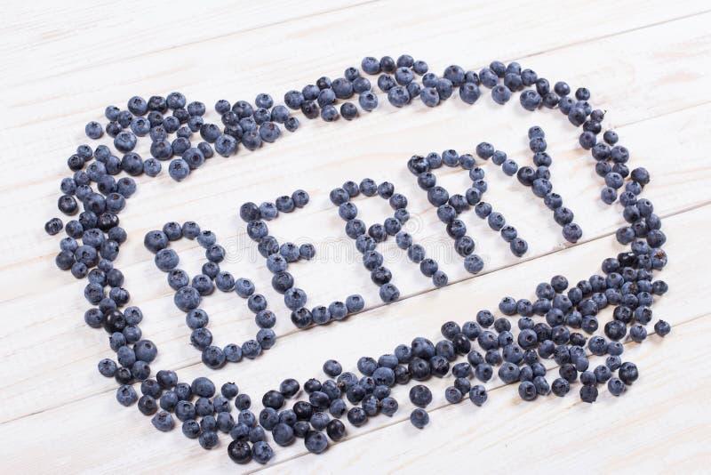 Fassen Sie Beere geschriebene Briefe mit Blaubeeren auf weißem hölzernem Eber ab lizenzfreie stockfotografie