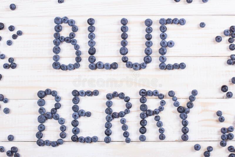 Fassen Sie Blaubeere geschriebene Briefe mit Blaubeeren auf weißem hölzernem ab lizenzfreie stockfotos