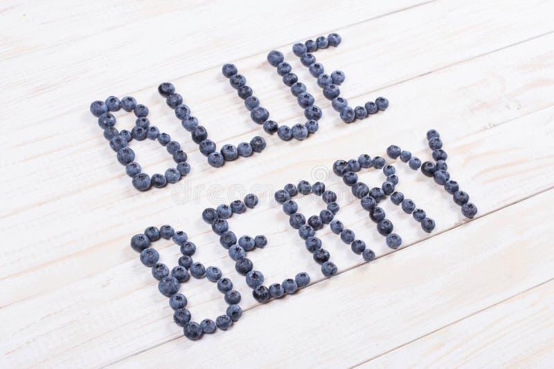 Fassen Sie Blaubeere geschriebene Briefe mit Blaubeeren auf weißem hölzernem ab stockbild