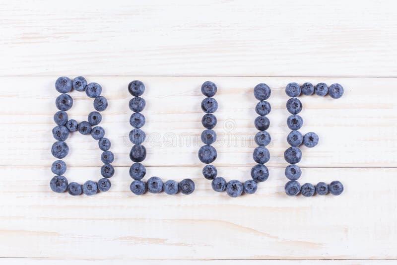 Fassen Sie blaue geschriebene Briefe mit Blaubeeren auf weißem hölzernem Brett ab stockbilder