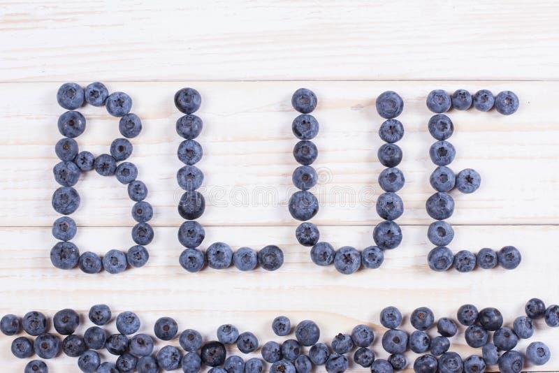 Fassen Sie blaue geschriebene Briefe mit Blaubeeren auf weißem hölzernem Brett ab stockfoto