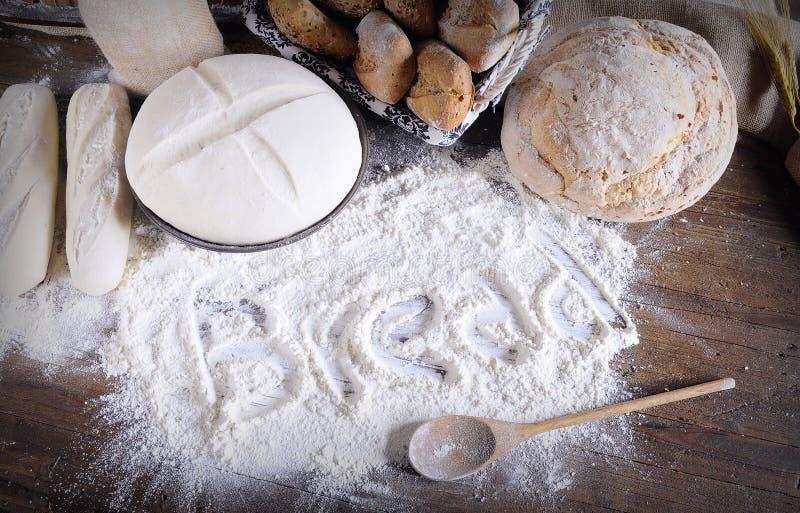 Fassen Sie 'das Brot ab', das auf das Mehl geschrieben wird, das auf Holztisch zerstreut wird lizenzfreie stockfotografie