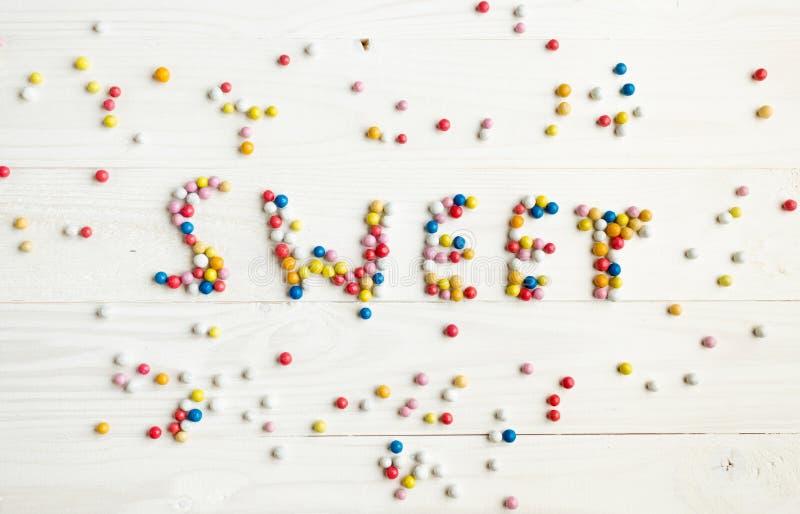 Fassen Sie den Bonbon ab, der durch kleine bunte Süßigkeiten auf weißes hölzernes Ba geschrieben wird stockbild