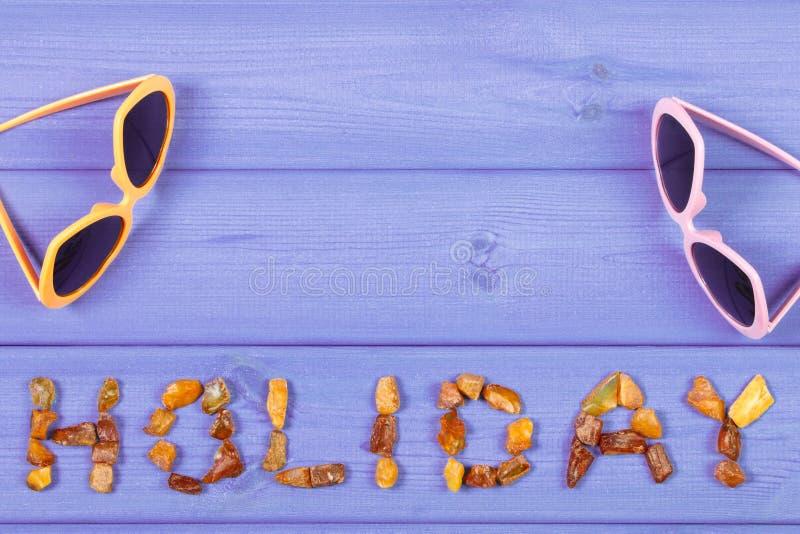 Fassen Sie den Feiertag ab, der von den bernsteinfarbigen Steinen und von der Sonnenbrille auf purpurroten Brettern, Sommerzeit,  stockbild