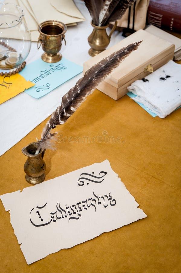 Fassen Sie die Kalligraphie ab, die auf altes Papier mit Kalligraphiewerkzeugen herein geschrieben wird lizenzfreies stockfoto