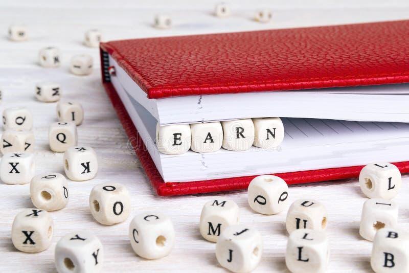 Fassen Sie Earn geschrieben in Holzklötze im roten Notizbuch auf weißes Holz ab lizenzfreies stockbild