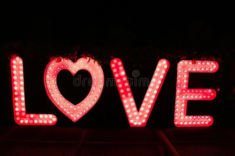 Fassen Sie Liebe von den großen Buchstaben mit glühenden Glühlampen auf einer Dunkelheit ab stockfotos