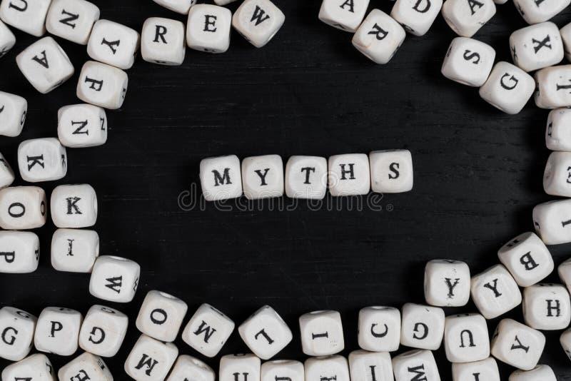 Fassen Sie MYTHEN auf hölzernen Würfeln auf einem schwarzen Holztisch ab lizenzfreies stockfoto