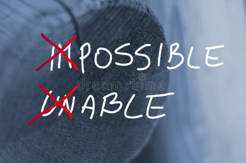 Fasst das unmögliche unfähige Konzept ab, das auf hölzernem Klotzhintergrund handgeschrieben ist stockbilder