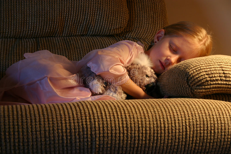 Fast Asleep in a Comfy Chair. A little girl dreams in a comfy armchair, too tired to make it to bed after a long day of play