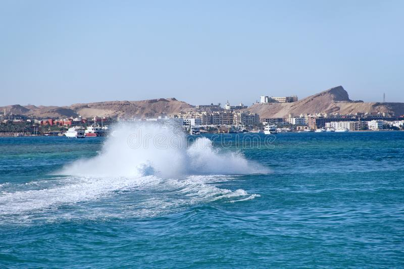 Fast boat making great splashes on sea water and rolling tourists on Red sea royalty free stock image