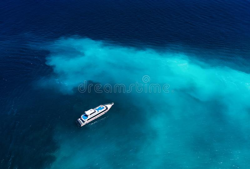 Fast boat at the sea in Bali, Indonesia. Aerial view of luxury floating boat on transparent turquoise water at sunny day. Seascape. From air. Top view from royalty free stock images