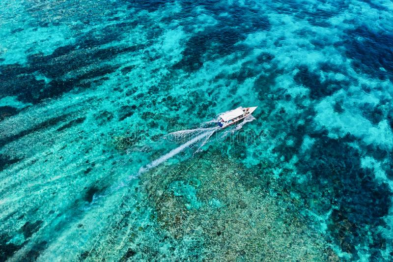 Fast boat at the sea in Bali, Indonesia. Aerial view of luxury floating boat on transparent turquoise water at sunny day. Seascape. From air. Top view from royalty free stock photography