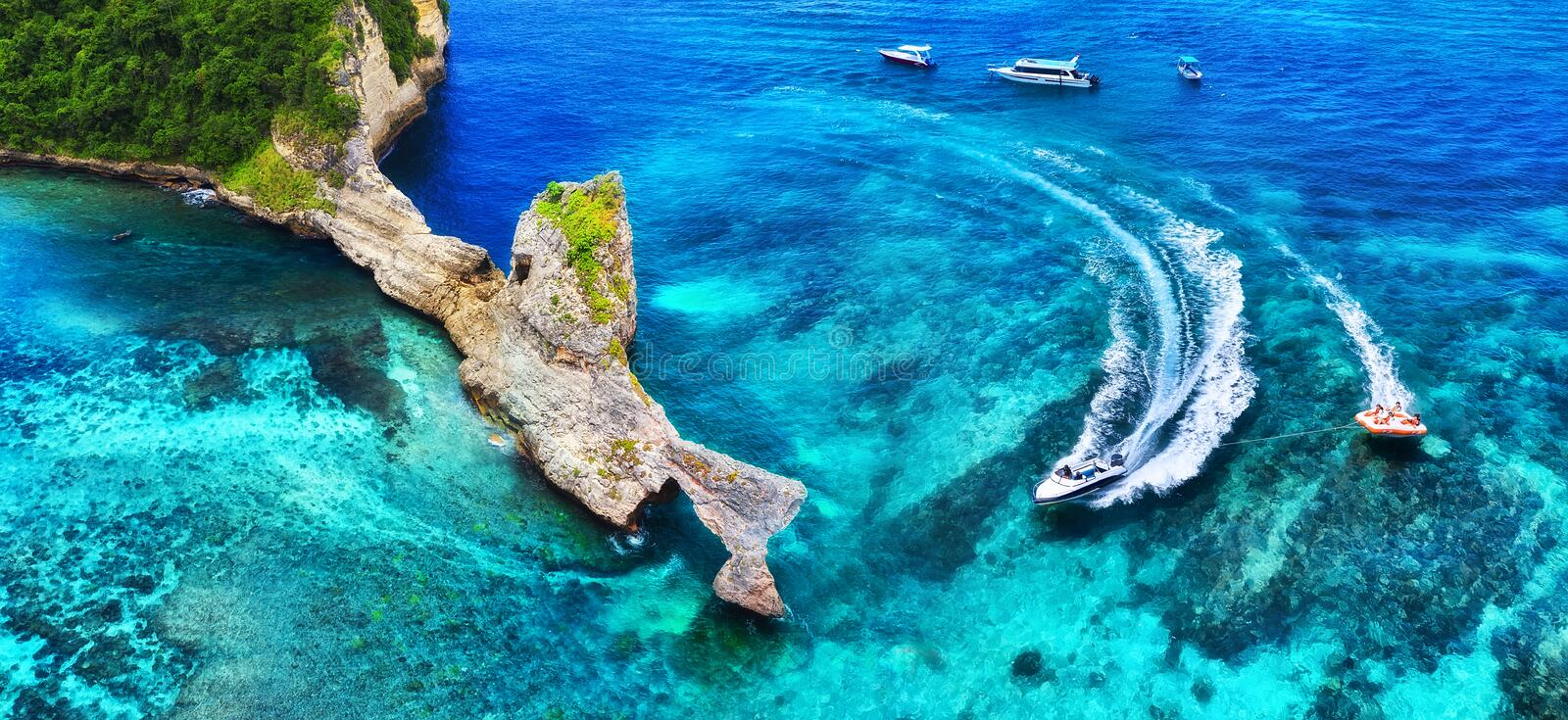 Fast boat at the sea in Bali, Indonesia. Aerial view of luxury floating boat on transparent turquoise water at sunny day. Panorami. C seascape from air. Top view stock image