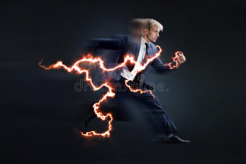 Fast business. Running businessman charged with lightning, concept royalty free stock photography