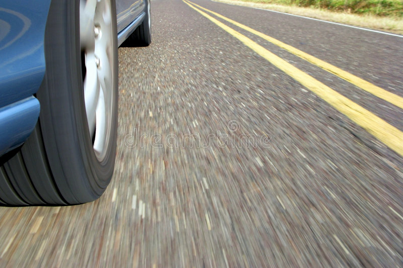 Fast Car Wheel Speeding on Country Road Pavement stock photography