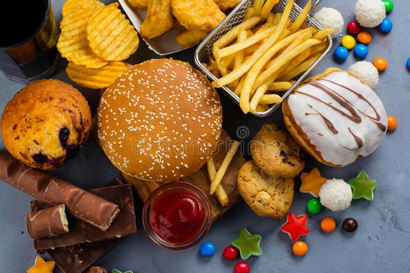 Fast carbohydrates food. Assortment of unhealthy products that`s bad for figure, skin, heart and teeth. Fast carbohydrates food. Space for text royalty free stock image