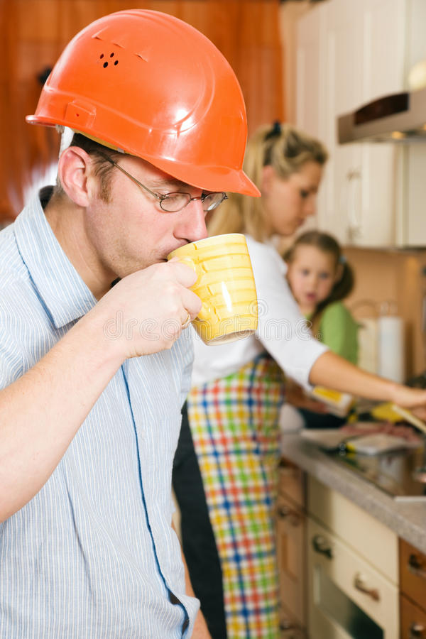 Fast coffee before starting to work. Construction worker with hardhat and father of a family having a morning cup of coffee before heading for his workplace royalty free stock photo