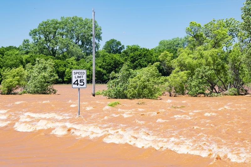 Fast current over road in Oklahoma. After severe flooding from midwestern storms stock photo