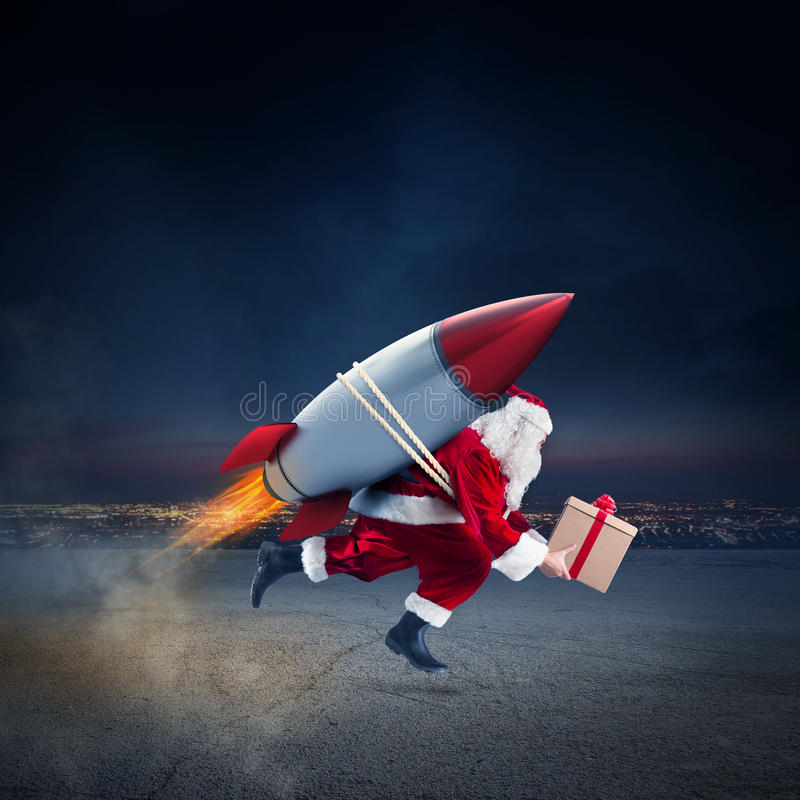 Fast delivery of Christmas gifts ready to fly with a rocket. Santa Claus with gift box ready to fly with a rocket in the sky royalty free stock photography
