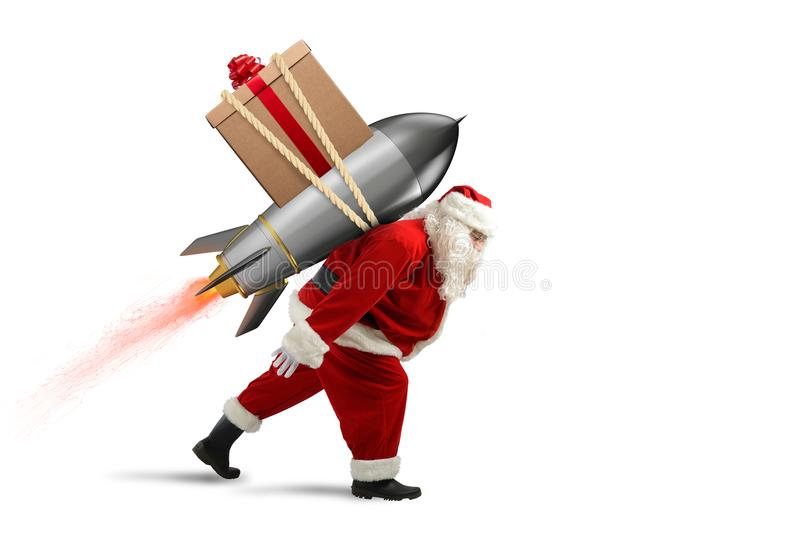 Fast delivery of Christmas gifts. Santa Claus ready to fly with a rocket. Santa Claus with Christmas gift box ready to fly with a rocket in the sky stock image