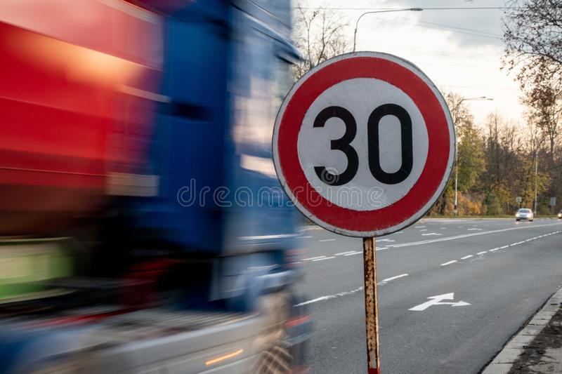 A fast driving blue speeding truck with motion blur effect near the traffic sign limiting the maximum speed to 30 kph royalty free stock photography