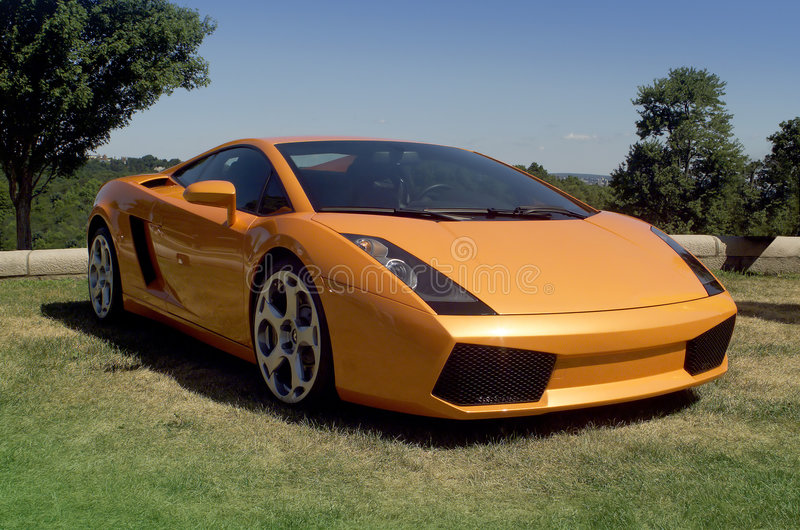 Fast exotic car. Dream car in metallic orange on lawn with blue sky stock photo