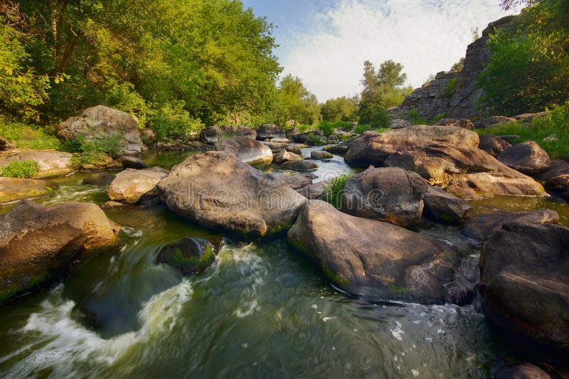 Fast flow of a mountain river. A narrow and fast mountain river flows between the rocks royalty free stock images