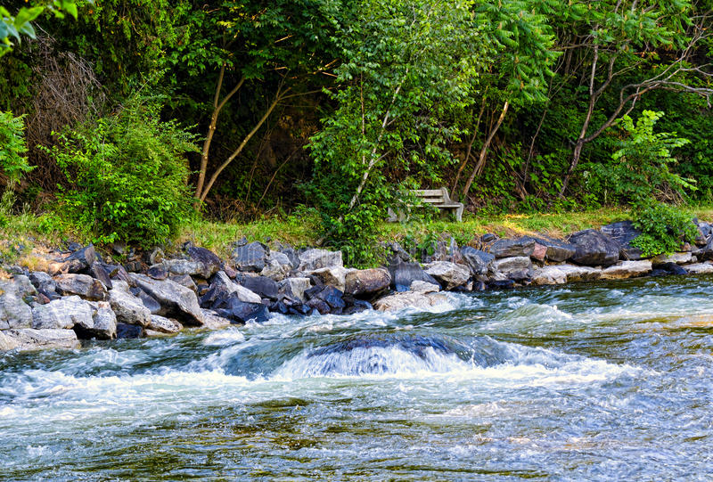 Fast flowing river and a bench on the river bank royalty free stock image