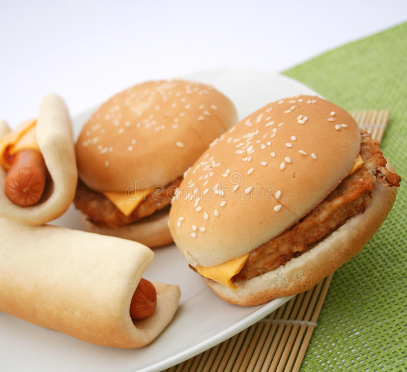Fast Food. A meal of fast food: cheeseburger and hot-dogs royalty free stock image
