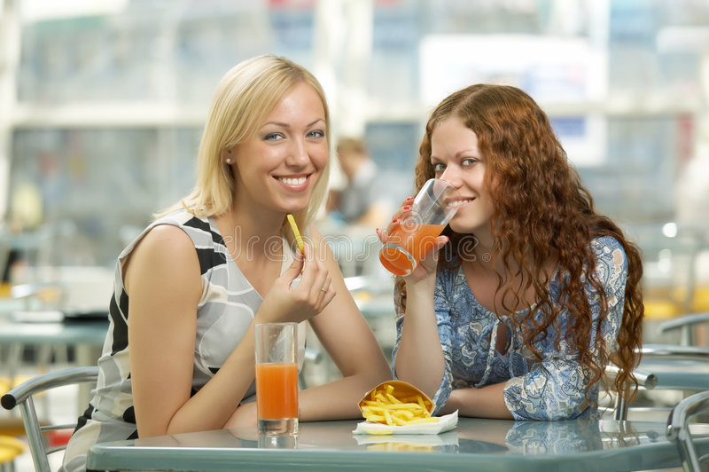 Fast food. Two girls eat in fast food cafe stock image
