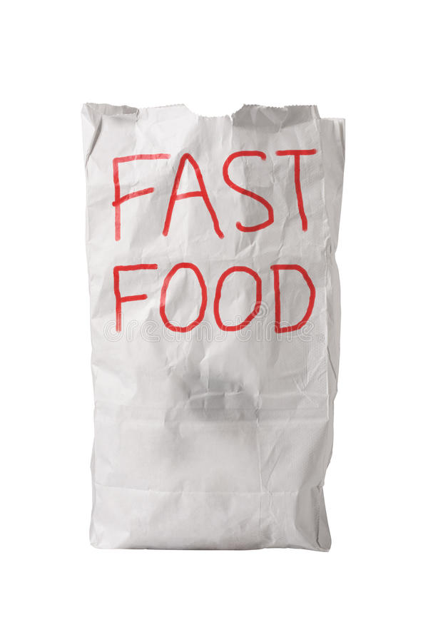 Fast Food Bag. A small white paper bag, wrinkled with some grease spots, with FAST FOOD written on it in big red letters, isolated on white stock photography