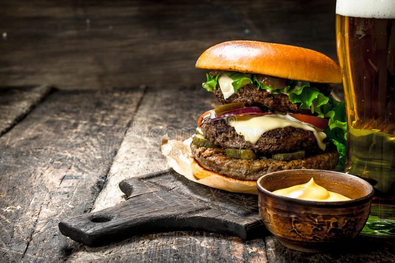 Fast food. A big burger with beef and a glass of beer. stock images