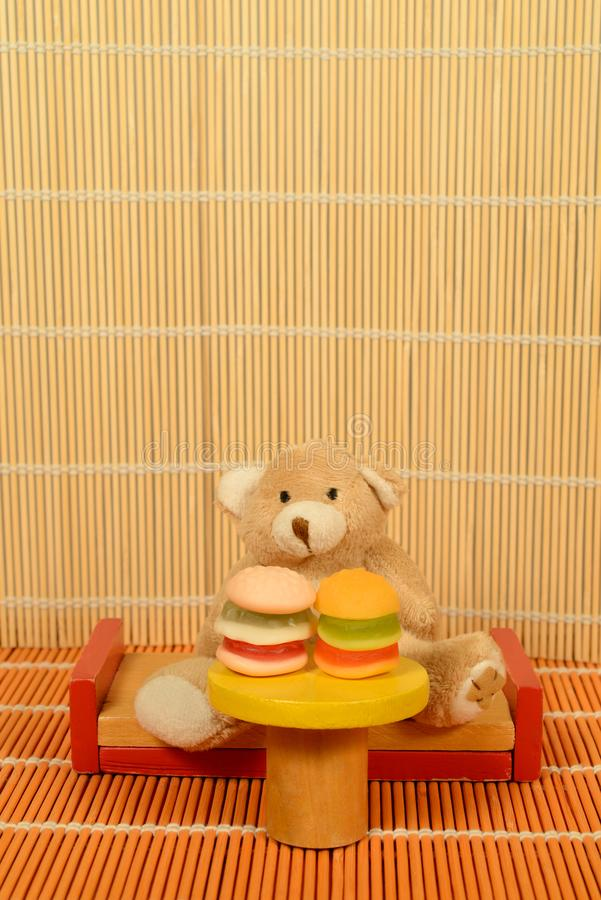 Fast food Bulimia Teddy bear sitting at table Hamburgers. A Teddy bear sitting in front of two hamburgers. Couch, table, bamboo flooring and background. Copy royalty free stock photo