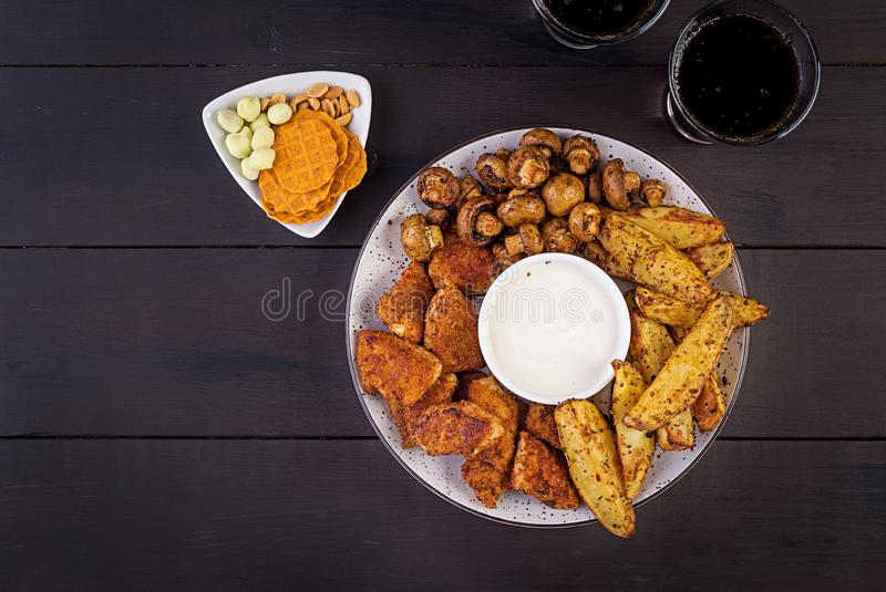 Fast food chicken nuggets with ketchup, french fries, baked mushrooms and cola. stock image