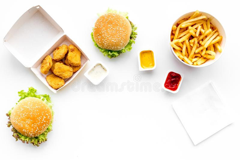 Fast food. Chiken nuggets, burgers and french fries on white background top view space for text stock photos