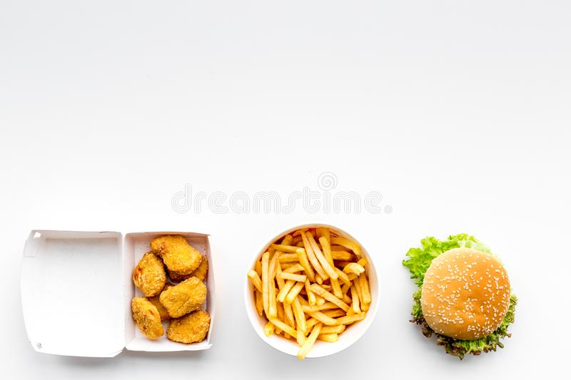Fast food. Chiken nuggets, burgers and french fries on white background top view space for text royalty free stock photos