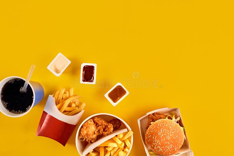 Fast food concept with greasy fried restaurant take out as onion rings, burger, fried chicken and french fries as a royalty free stock photos