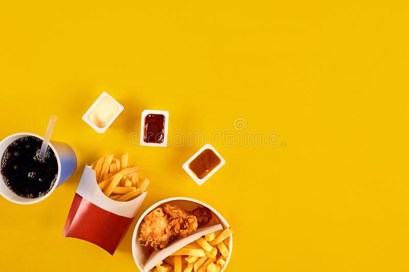 Fast food concept with greasy fried restaurant take out as onion rings, burger, fried chicken and french fries as a. Symbol of diet temptation resulting in stock photography
