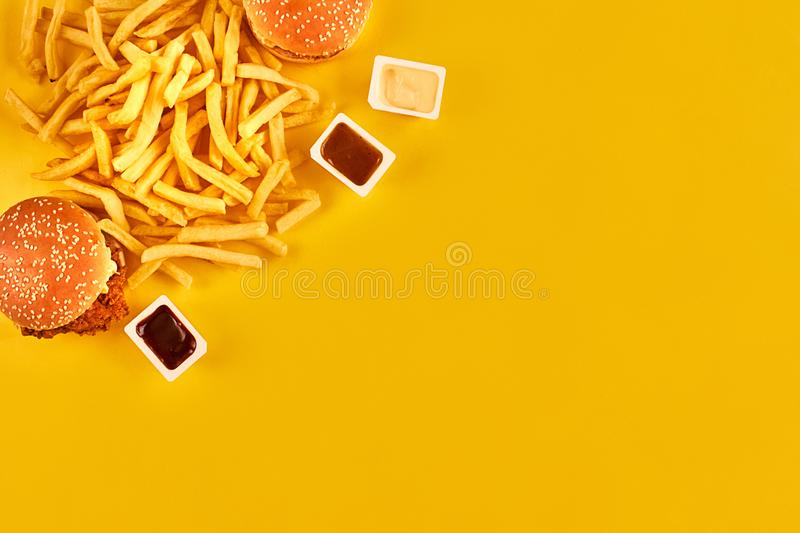 Fast food concept with greasy fried restaurant take out as onion rings, burger, fried chicken and french fries as a. Symbol of diet temptation resulting in stock image