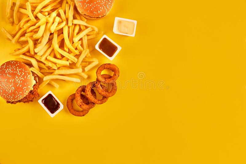 Fast food concept with greasy fried restaurant take out as onion rings, burger, fried chicken and french fries as a. Symbol of diet temptation resulting in royalty free stock image