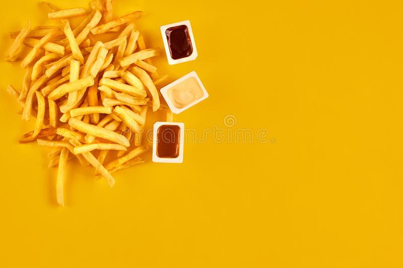 Fast food concept with greasy fried restaurant take out as onion rings, burger, fried chicken and french fries as a. Symbol of diet temptation resulting in royalty free stock photo