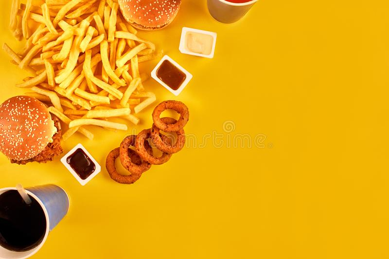 Fast food concept with greasy fried restaurant take out as onion rings, burger, fried chicken and french fries as a. Symbol of diet temptation resulting in royalty free stock photos