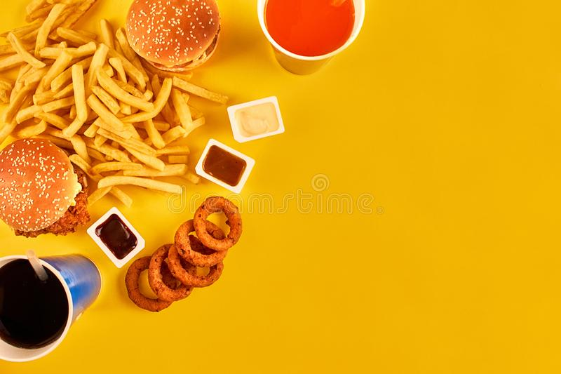 Fast food concept with greasy fried restaurant take out as onion rings, burger, fried chicken and french fries as a. Symbol of diet temptation resulting in royalty free stock images